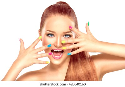 Beauty Girl Face with Colorful Nail polish. Colourful Studio Shot of young Woman. Vivid Colors. Colourful Manicure and fashion Makeup. Rainbow Color. Beautiful lady touching her face isolated on white