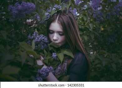 beauty girl in fashion style smells lilac flowers outdoors