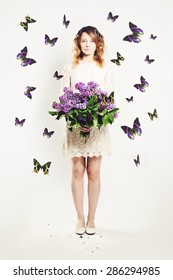 Beauty Girl with Flowers and  Butterfly. Beautiful Model woman with Blooming flowers on her hand. Nature Hairstyle. Summer Fashion Creative Background. Vogue Style Portrait