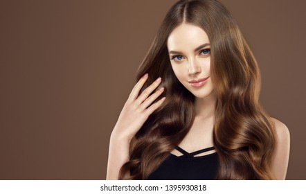 Beauty girl with long  and   shiny wavy hair .  Beautiful   woman model with curly hairstyle .