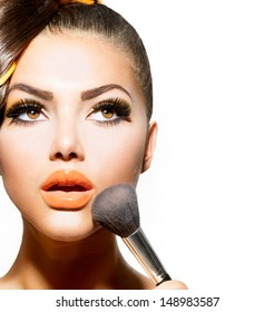Beauty Girl with Makeup Brush. Bright Holiday Make-up for Brunette Woman with Brown Eyes. Orange and Yellow Make up. Beautiful Face. Makeover. Perfect Skin. Applying Makeup
