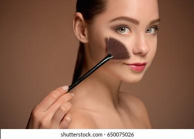 Beauty Girl with Makeup Brush. Perfect Skin. Applying Makeup