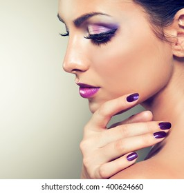 Beauty girl model with violet manicure  on the nails.  Cosmetics and cosmetology .