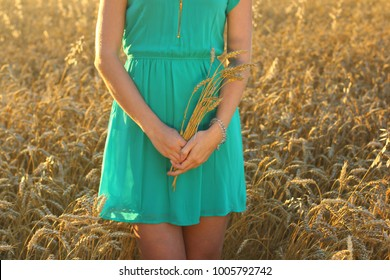Beauty Girl Outdoors enjoying nature. Teenage Model girl in blue dress on the summer Field, Sunset Light.