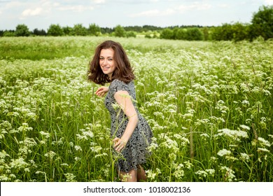 Beauty Girl Outdoors enjoying nature. Beautiful woman jumping on summer Field with blooming wild flowers, Sun Light. Free Happy Woman