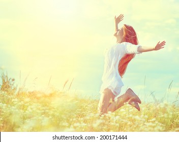 Beauty Girl Outdoors enjoying nature. Beautiful Teenage Model girl in white dress jumping on summer Field with blooming wild flowers, Sun Light. Free Happy Woman. Toned in warm colors