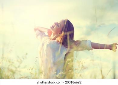 Beauty Girl Outdoors enjoying nature. Beautiful Teenage Model girl in white dress having fun on summer Field with blooming flowers, Sun Light. Sunrise. Glow Sun. Free Happy Woman