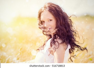 Beauty girl outdoors enjoying nature. Closeup portrait of young beautiful lady with curly hair. Woman on wheat field blurred background. lens flare toned. beauty girl posing. Beauty woman freedom.