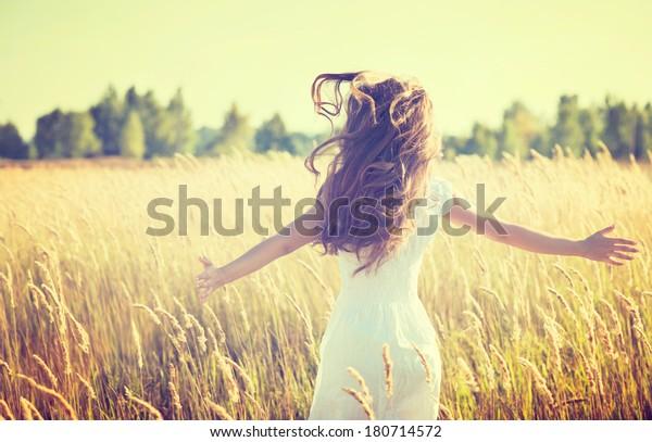 Beauty Girl Outdoors profitant de la nature. Belle fille Modèle Adolescent en robe blanche courant sur le Champ de Printemps, Lumière du Soleil.