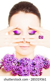 Beauty Girl Portrait with Colorful Makeup, Nail Polish, ring Accessories and Purple Flowers. Colourful eye shadows Make-up