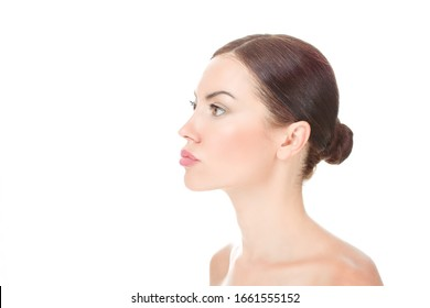Beauty girl posing in side profile. Close up portrait serious beautiful woman looking to side in profile view showing clean skin fresh face, nude body isolated on white background with copy space.
