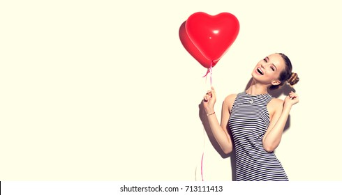 Beauty girl with red heart shaped air balloon laughing over white background. Beautiful Happy woman on birthday party, Love, Valentine's Day party. Joyful model having fun, celebrating with balloons