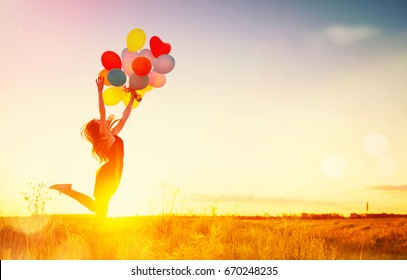 Beauty girl running and jumping on summer field with colorful air balloons over Sunset clear sky. Silhouette, Happy young healthy woman enjoying nature outdoors. Running and Spinning female. Flying