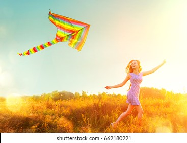 Beauty girl in short dress running with kite on the field. Beautiful young woman with flying colorful kite over clear blue sky. Free, freedom concept. Emotions, healthy lifestyle