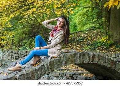 beauty girl sitting on a bridge in the autumn park