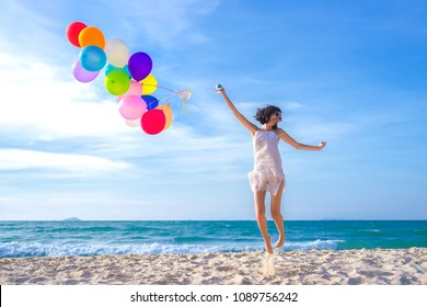Beauty girl smiling and jumping on the beach at the day time. with colorful air balloons Very much.