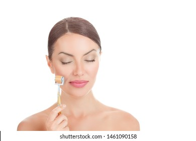 Beauty girl using derma roller. Close up portrait smiling cute beautiful woman, showing mezo-roller, for clean skin fresh face, eyes closed, body isolated on white background with copy space
