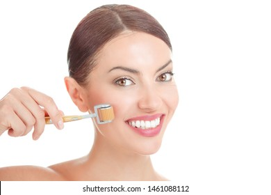 Beauty girl using skin anti aging needles roller. Close up portrait smiling cute beautiful woman, showing mezo-roller, for clean skin fresh face, body isolated on white background with copy space