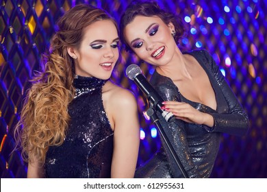 Beauty girls with a microphone singing over holiday blinking background. Disco party. Celebration