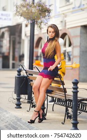 Beauty Glamor young Woman in a cozy city. leaned her elbows on the bench. Long hair. Fashionable lady with a beautiful hairdo, makeup. against the background of a tourist city..
