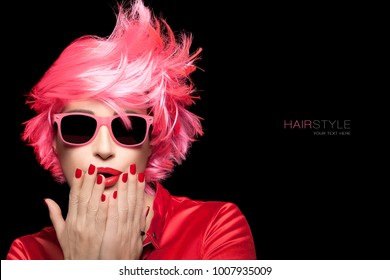 Beauty and glamour portrait of a woman with dyed pink hair wearing matching trendy sunglasses and stylish top holding her hands with red manicured nails to her mouth and lips with red lipstick