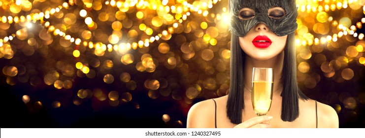 Beauty Glamour Woman celebrating with champagne, wearing carnival mask, party, drinking sparkling wine over holiday glowing background. Christmas and New Year Holiday celebration. Widescreen