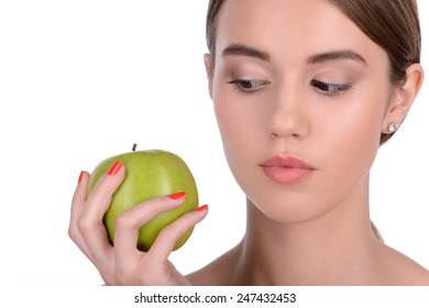 Beauty with green apple. Beautiful young woman holding a green apple and looking at it while standing isolated on white