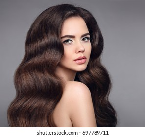 Beauty hair. Brunette girl portrait with long shiny wavy hair