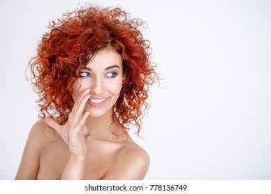 Beauty, hair concept. Beautiful joyful young woman with bright red curly hair and healthy shiny skin. White background. Copy space.