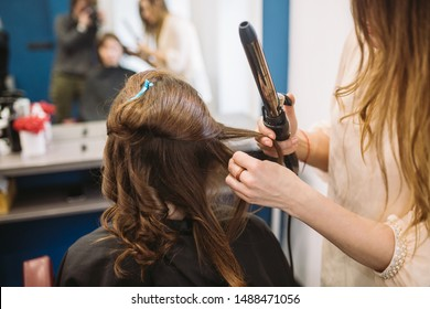 beauty, hairstyle concept, happy young woman and hairdresser with hair iron making hairdo at hair salon. Woman Having Hair Stylized Hairdresser. Smoothes Hair Curling. Stylist Using Tool for Modeling.