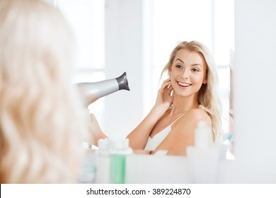 beauty, hairstyle, morning and people concept - smiling young woman with fan blow drying her hair looking to mirror at home bathroom