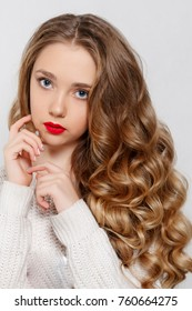 beauty, hairstyle and people concept - Beautiful model brunette with long curled hair . Girl big necklace with beads and chain . Jewelry and accessories .Hairstyle wavy curls. girl white long sweater