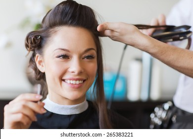 beauty, hairstyle and people concept - happy young woman and hairdresser with hair iron making hairdo at hair salon