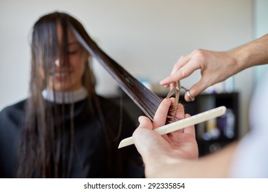 beauty, hairstyle and people concept - happy young woman and hairdresser hands with scissors and comb cutting hair tips at salon