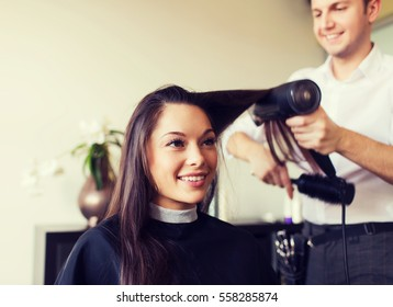 beauty, hairstyle and people concept - happy young woman and hairdresser with fan making hot styling at hair salon