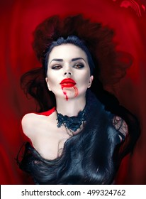 Beauty Halloween Sexy Vampire Woman with dripping blood on her mouth lying in a bath full of blood. Vampire Fashion Art design scene, sexy female vampire girl in a bloody bath. Desire, thirst concept