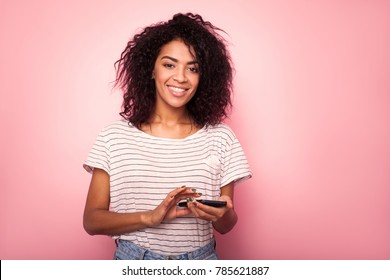 Beauty happy african woman looking at phone and writing message isolated pink background.