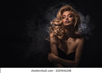 Beauty headshot of fashion blonde model on dark smoked background