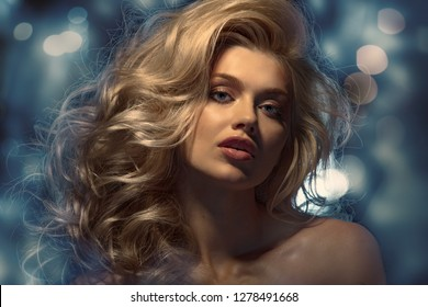 Beauty headshot of fashion blonde model on dark background