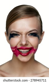 Beauty and health clean Skin of evil Girl with smoky Eyes and red Lips with smeared Mascara and red Lipstick scary laughs .
