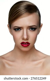 Beauty and health clean Skin of young female Model with smoky Eyes and red Lips with negative emotions.