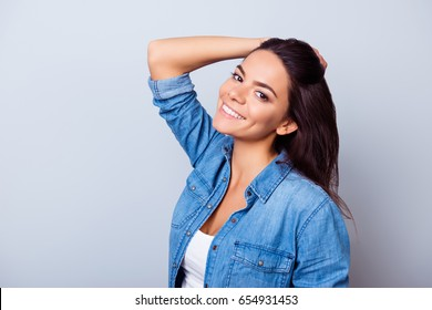 Beauty and health concept. Young pretty latin mulatto lady is touching  her healthy nice hair, looking straight in the camera. So fresh, attractive and healthy, wearing jeans casual shirt
