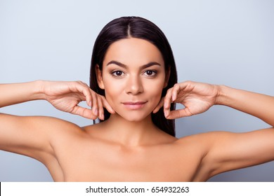 Beauty and health concept. Young pretty latin mulatto lady is touching gently her attractive healthy bronze skin, looking straight in the camera. So fresh, attractive and healthy