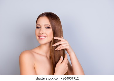 Beauty and health industry concept. Close up cropped photo of beautiful young attractive girl touching her healthy nice hair as a silk on light blue background