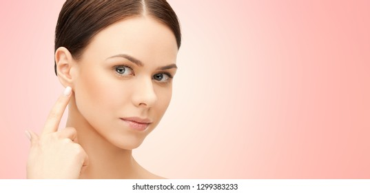 beauty, hearing and plastic surgery concept - face of beautiful young woman pointing finger to earlobe over pink background