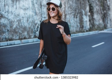 Beauty hipster woman outdoor portrait, sport, skateboard,Beautiful sexy young girl in short shorts walking with longboard in sunny weather.Leisure.Healthy lifestyle. Extreme sports.Fashion look