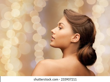 beauty, holidays, people and hairstyle concept - beautiful young woman with bare shoulders over beige lights background