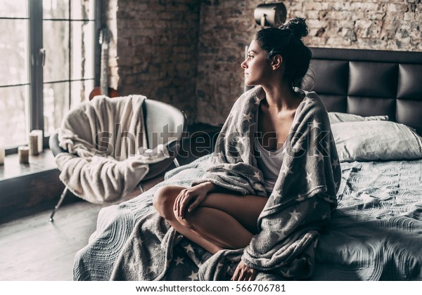 Beauty at home. Gorgeous young woman covered with blanket looking through window while sitting in bed at home