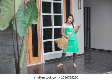 Beauty housewife hold a broom and smile and action in front of the camera