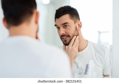 beauty, hygiene and people concept - smiling young man looking to mirror at home bathroom